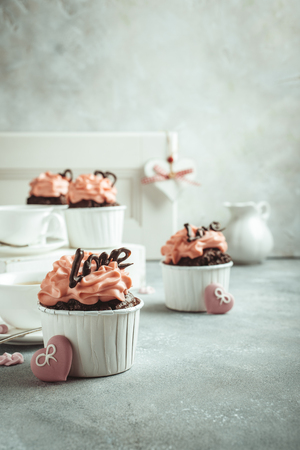 afternoon fancy cake: Beautiful chocolate cupcake, pink cream and heart on gray stone background. Valentines, Mother Day, wedding concept with copy space. Retro style toned.