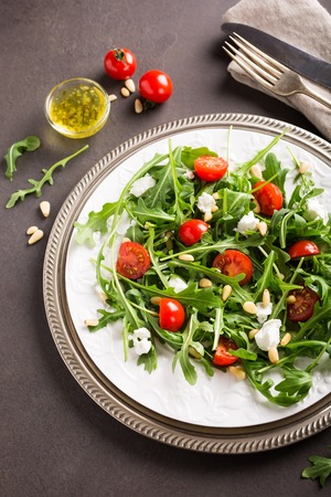 fresh vegetable salad with rucola, tomatos and goat cheese. Healthy food concept.