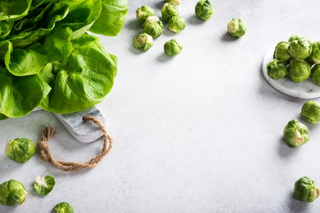 Background with assorted green vegetables, fresh lettuce salad and Brussels sprouts on light gray stone table. Healthy food concept with copy space.