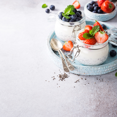 Chia seed pudding with berries in glass jar. Superfoods concept with copy space.
