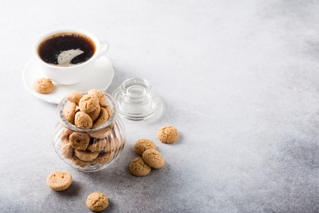 Amaretti cookies in glass pot with white cup of coffee on light gray background with copy space. High angle view