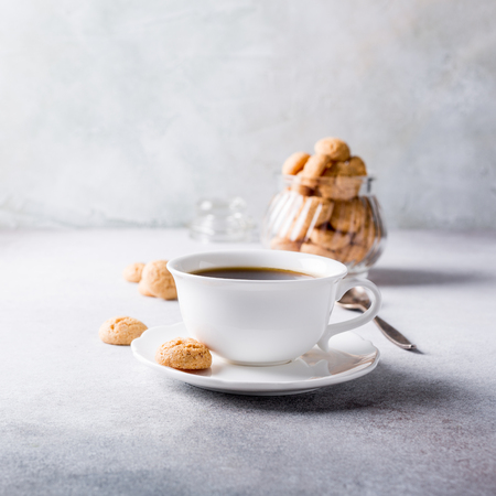 amaretto: White cup of coffee with amaretti cookies on light gray background with copy space.