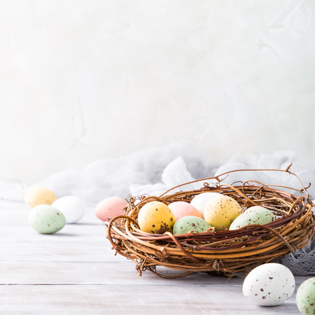 Ostern-Zusammensetzung von bunten Wachteleiern im Nest auf dem hellen hölzernen Hintergrund. Ferienkonzept mit Kopienraum.