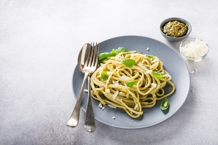 Homemade pasta, spaghetti, linguine with green pesto and basil. Italian healthy food concept with copy space. Stock Photo