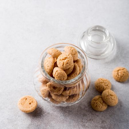 Biscotti di Amaretti in vaso di vetro su fondo grigio chiaro con lo spazio della copia. Veduta dall'alto