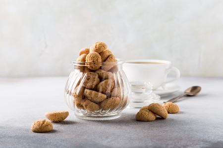Biscotti di Amaretti in vaso di vetro con la tazza di caffè bianca su fondo grigio chiaro con lo spazio della copia.