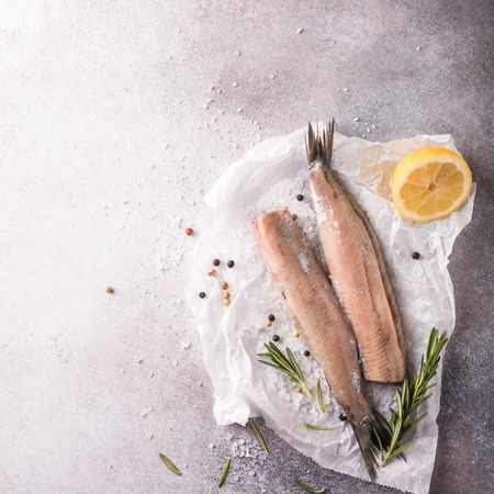 Freshly salted herring with salt, lemon ans rosemary on gray background with copy space. Traditional Dutch delicacy. Retro style toned. Top view. Reklamní fotografie