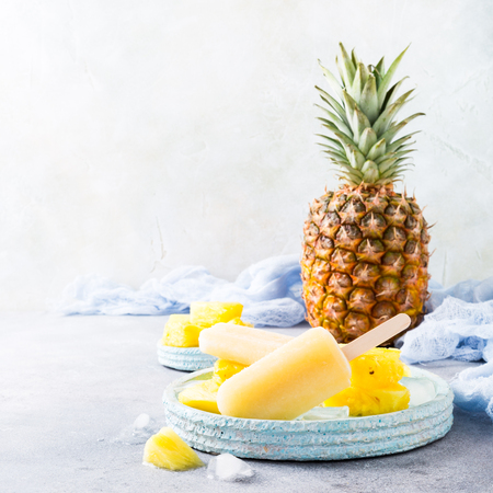 Delicious homemade pineapple popsicles on light blue plate on gray background. Summer food concept with copy space. Stok Fotoğraf