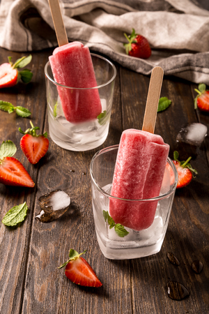 Retro style toned photo of strawberry popsicles in glass with ice on old wooden background. Healthy summer food concept. Stock Photo