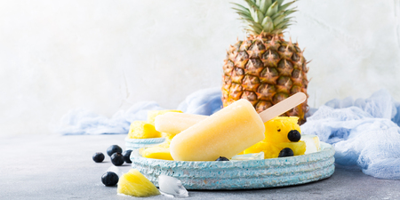 Fresh frozen juice ice cream, pineapple popsicles with blueberries on light blue plate. Summer food concept with copy space.