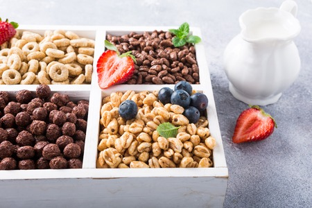 Milk jug and variety of cold quick breakfast cereals with berries in white wooden box, healthy eating concept, selective focus.