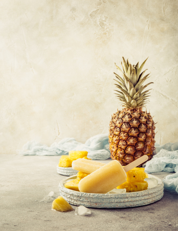 Retro style toned photo of homemade frozen pineapple juice popsicles. Summer food concept with copy space.