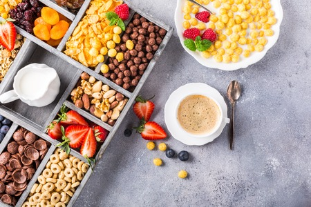 Healthy breakfast with coffee, variety of cold quick cereals and berries in old gray wooden box, selective focus. Copy space. Top view. Stock Photo