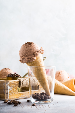 measuring cup: Waffle cone with coffee ice cream in glass and ingredients in wooden tray. Healthy summer food concept with copy space. Stock Photo