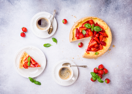 Overhead shot of cups of coffee, delicious homemade strawberry cheesecake and flowers on light gray background. Top view, flat lay.