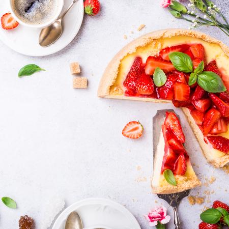 Tiro aéreo das xícaras de café, do bolo de queijo caseiro delicioso da morango e das flores na luz - fundo cinzento. Vista superior, lay plana. Copie o espaço. Foto de archivo - 79730297