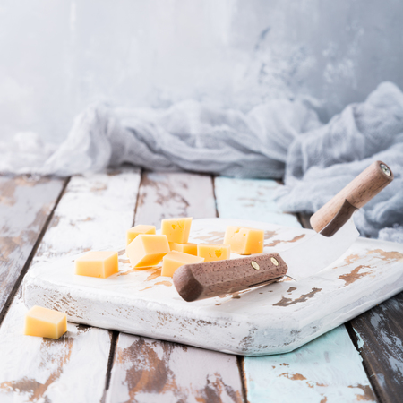 Delicious dutch gouda cheese with cheese cubes and special knife on oud wooden table. Copy space. Stock Photo