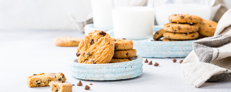 Chocolate chip cookies on blue stone plate with glass of milk on light gray background. Selective focus. Copy space. Stock Photo
