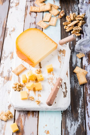 hard: Delicious dutch gouda cheese with cheese blocks, crackers, walnuts and special knife on old wooden table.