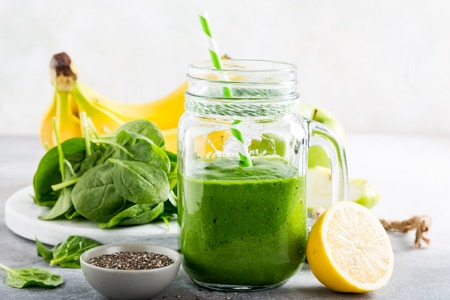 Healthy green smoothie with spinach, banana, lemon, apple and chia seeds in glass jar and ingredients. Detox, diet, healthy, vegetarian food concept.