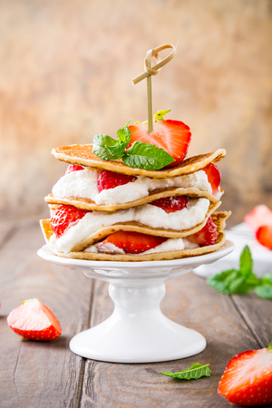 recipe decorated: Pancakes mini cake with yogurt and strawberries on white porcelain cake stand. Childrens party concept, copy space.