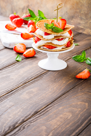 Small cake made of pancakes with cream and strawberries on white porcelain cake stand. Childrens party background. Healthy food concept, copy space. Stock Photo