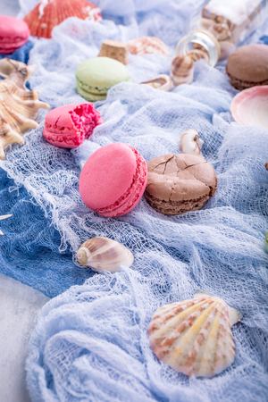 Assorted almond cookies macaroon with sea decoration on light gray stone background. Party food concept. Stock Photo