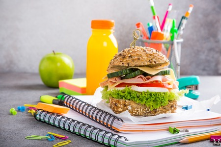 Healthy lunch for school with sandwich, fresh apple and orange juice. Assorted colorful school supplies. Copy space. Stok Fotoğraf - 81702928