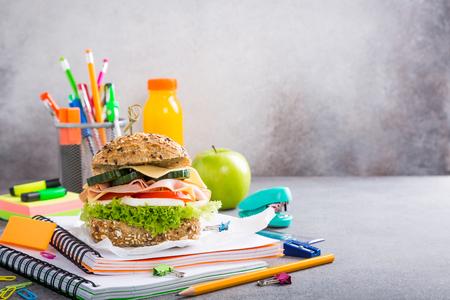 Almuerzo saludable para la escuela con sandwich, manzana fresca y jugo de naranja. Surtido de útiles escolares coloridos. Copia espacio Foto de archivo - 82174450