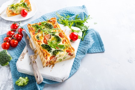 Delicious vegetarian homemade pie, Quiche with cherry tomatoes, broccoli and herbal cheese on old white cutting board. Healthy food concept. Copy space. Stock Photo - 82800414