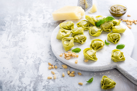 tortellini: Homemade raw Italian tortelloni and ingredients for green pesto on marble cutting board on light gray background. Healthy food concept. Selective focus. Copy space.
