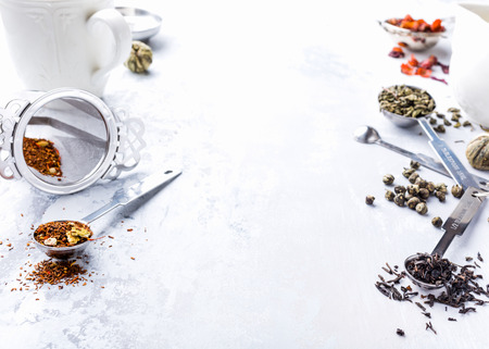 Background with different types of tea leaves, black, green, rooibos and strawberry with tea making facilities. Healthy drink concept. Copy space. Stock Photo