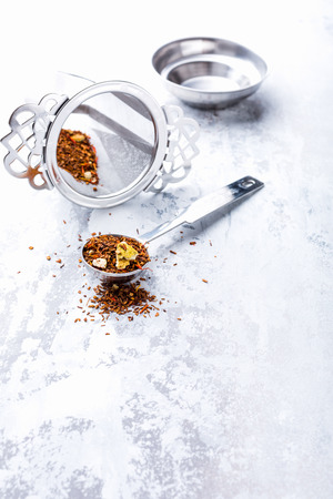 Rooibos tea in a measuring spoon with sieve on light gray background. Healthy drink concept, copy space.