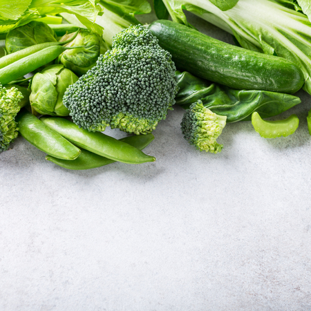 Background with assorted green vegetables, salad, broccoli, cucumber, peas and Brussels sprouts on light gray stone table top. Healthy food concept with copy space.