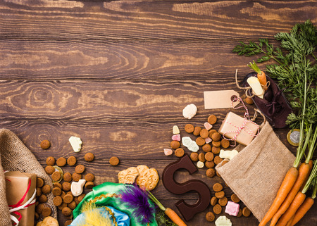 Holenderski wakacje Sinterklaas tło z prezentami, pepernoten, list czekoladowy, słodycze i buty dla dzieci z marchewką dla konia Mikołaje. Mieszkanie leżał z miejsca na kopię.