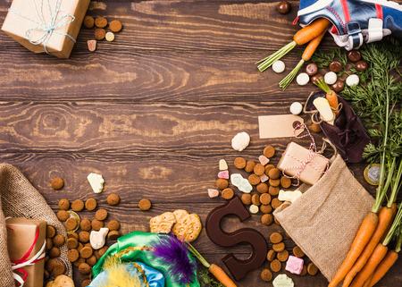 Feriado holandês Sinterklaas fundo com presentes, pepernoten, carta de chocolate, doces e sapato infantil com cenouras para cavalo de Papai Noel. Postura plana com espaço de cópia. Foto de archivo - 87246246