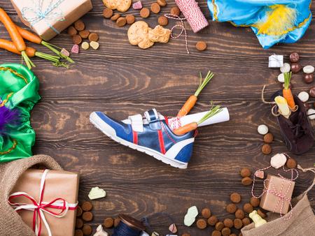 Nederlandse vakantie Sinterklaas achtergrond met geschenken, pepernoten, snoepjes en kinderschoen met wortelen op oude houten tafel. Vlak liggen met kopie ruimte. Bovenaanzicht.