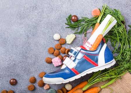 Dutch holiday Sinterklaas composition with childrens shoe with carrots for Santas horse and sweets with copy space. Top view.
