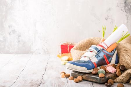 オランダの休日の Sinterklaas の子供の靴とコピースペースでサンタの馬とお菓子のためのニンジンとコンポジション 写真素材