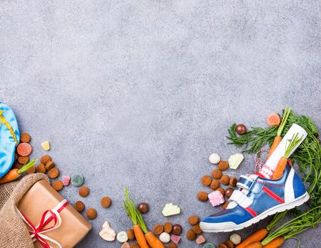 Nederlandse vakantie Sinterklaas achtergrond met kinderschoen met wortelen voor Santas paard, pepernoten en snoepjes met kopie ruimte. Bovenaanzicht. Stockfoto