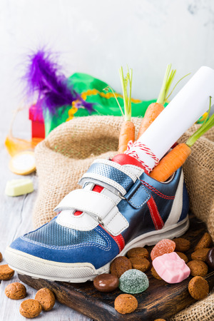 Dutch holiday Sinterklaas composition with childrens shoe with carrots for Santas horse and sweets with copy space