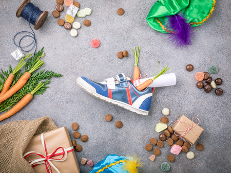 Dutch holiday Sinterklaas background with gifts, pepernoten, sweets and childrens shoe with carrots for Santas horse. Flat lay with copy space. Top view. Stockfoto