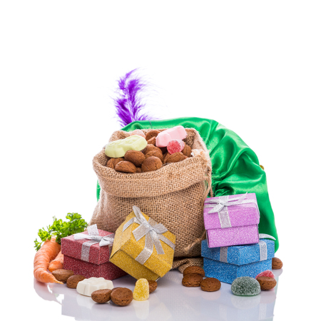 Burlap sack with traditional sweets for the Dutch holiday Sinterklaas and colorful gifts over white. Festive concept with copy space. Stock Photo