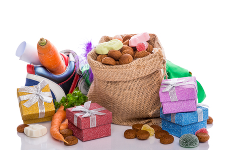 Jutezak met traditionele snoepjes voor de Nederlandse Sinterklaasvakantie en kleurrijke geschenken over wit. Feestelijk concept met kopie ruimte. Stockfoto