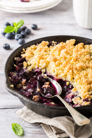 Coconut crumble in cast iron pan with fresh apples and blueberry. Healthy food concept.