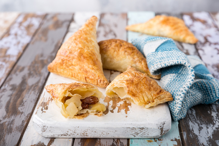 Puff pastry triangles filled with apples, dutch appelflappen on old cutting board. Homemade food concept with copy space.