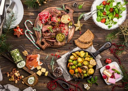 Flache Lage des themenorientierten Abendtischs Delicious Christmas mit gebratenem Fleischsteak, -aperitifs und -nachtischen. Draufsicht. Ferienkonzept.