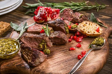 Bife da carne do canguru com pesto e a romã verdes na placa de corte de madeira. Conceito de comida de férias Helthy. Foco seletivo. Foto de archivo - 88608484