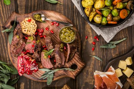 緑のペストと木製のまな板にザクロとカンガルーの肉のステーキです。Helthy 休日食品のコンセプト。平面図です。