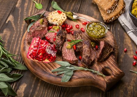 緑のペストと木製のまな板にザクロとカンガルーの肉のステーキです。Helthy 休日食品のコンセプト。選択と集中。